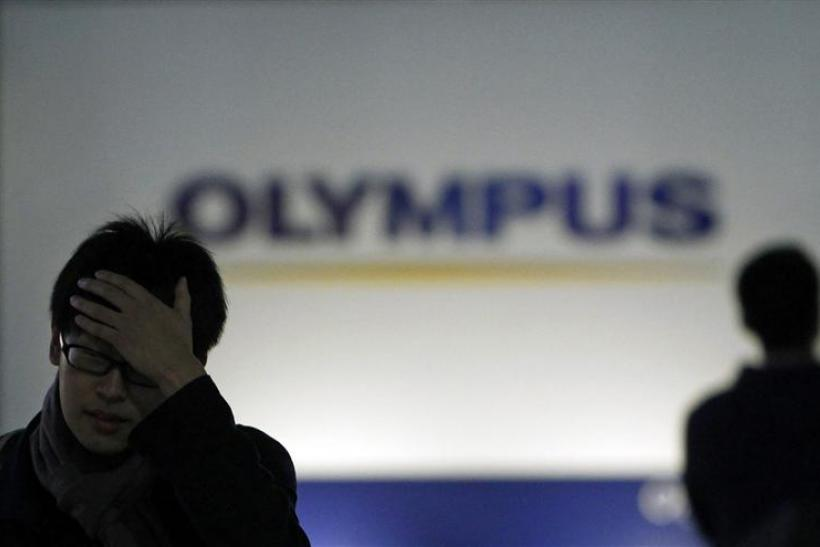 Men walk past a sign of Olympus Corp outside the company's showroom in Tokyo