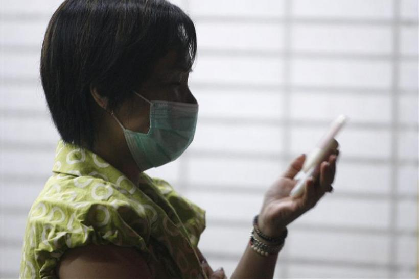 A woman wearing a medical mask uses her mobile phone outside a hospital in Taiwan