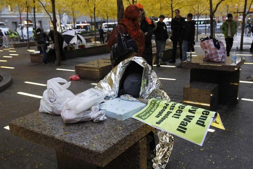 An Occupy Wall Street demonstrator sleeps next to a table at Zuccotti Park in New York