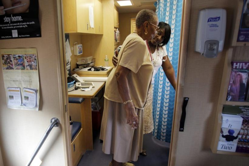 Healthcare educator Rainelle White (rear) checks the weight of client Norma Ferguson in the Family Van in Boston