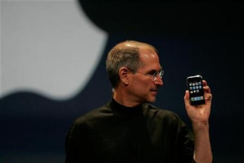 Apple Computer Inc. Chief Executive Officer Steve Jobs holds the new iPhone in San Francisco, California