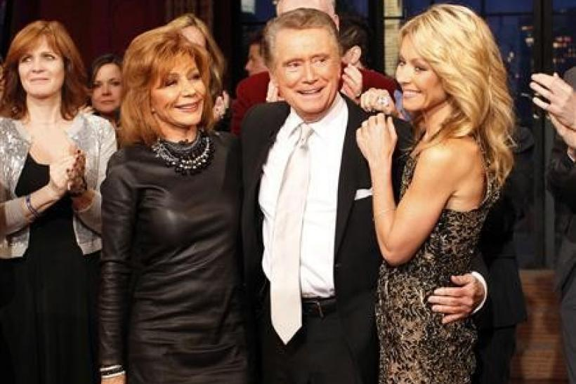 """Television host Regis Philbin (C) says goodbye with his wife Joy Philbin (L) and co-host Kelly Ripa (R) during his final show of """"Live With Regis and Kelly"""" in New York, November 18, 2011. After nearly three decades hosting the show that became"""