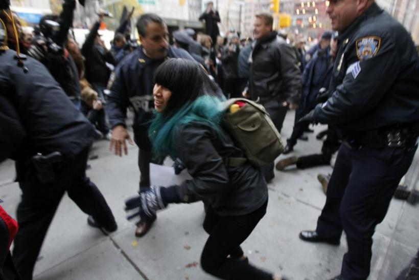 An Occupy Wall Street demonstrator is pushed out of the way by police officers as they make an arrest in New York