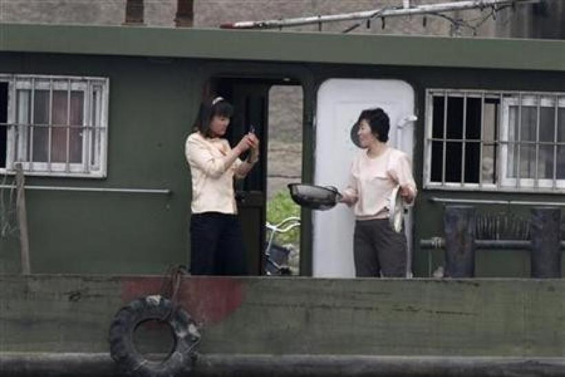 A North Korean woman uses mobile phone to take picture of her compatriot friend on a boat along Yalu River near the North Korean town of Sinuiju, opposite the Chinese border city of Dandong, May 20, 2011.