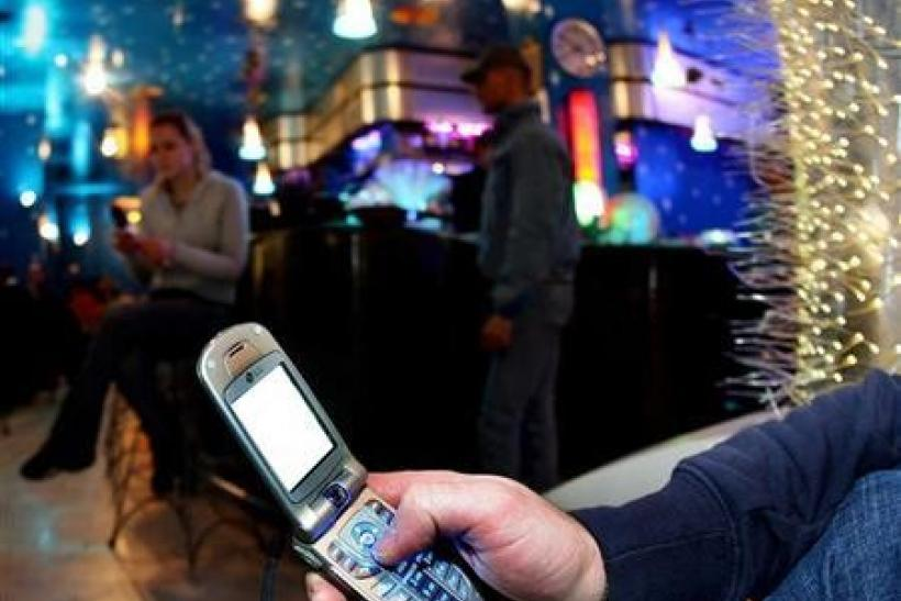 A man keys in a message onto a mobile phone in a Milan bar March 3, 2006.