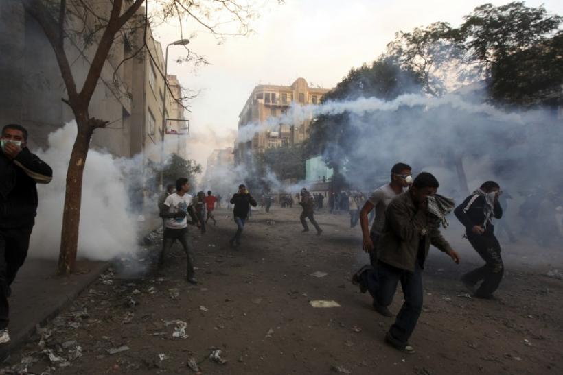 Protesters flee from tear gas fired by riot police during clashes along a road near Tahrir Square