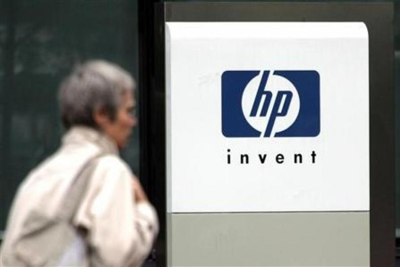 A woman walks past the Hewlett Packard logo at its French headquarters in Issy le Moulineaux, western Paris, in this September 16, 2005 file photograph.