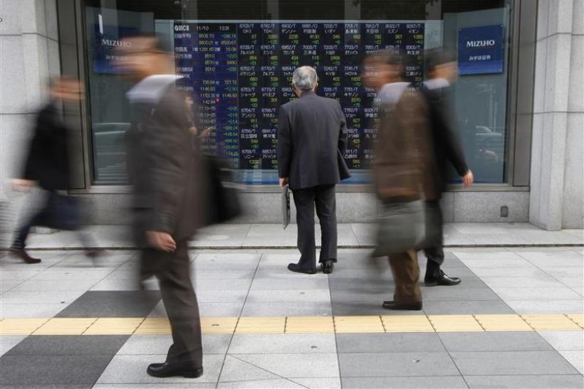 Man looks at an electronic board displaying stock prices outside a brokerage in Tokyo