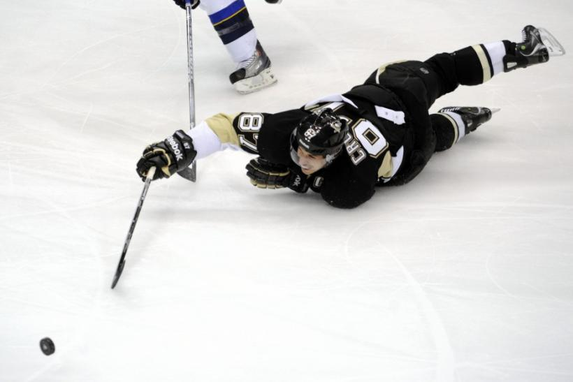 Pittsburgh Penguins' Crosby reaches for the puck after being tripped in the second period of his NHL hockey game against the St. Louis Blues in Pittsburgh