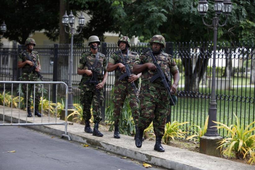 Trinidad and Tobago soldiers patrol the residence of Prime Minister Kamla Persad-Bissessar after her news conference in Port of Spain