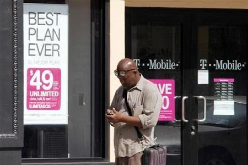 A man checks his mobile phone as he walks past a T-Mobile store in downtown Los Angeles, California August 31, 2011.
