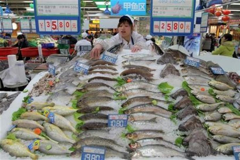 A shop assistant arranges fish for sale at a supermarket in Hangzhou, Zhejiang province January 14, 2011.