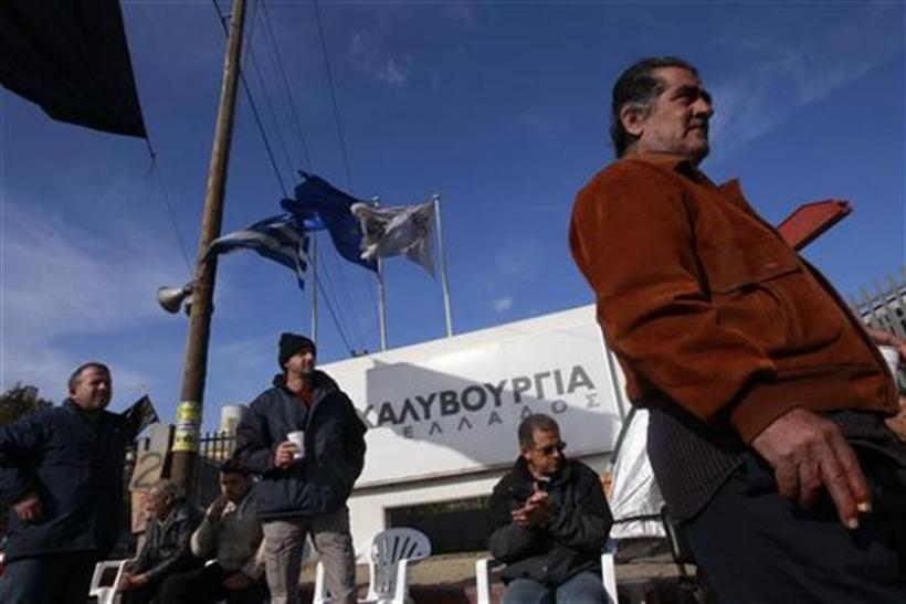 Workers of the Hellenic Steel Company stand outside a factory during a strike at Aspropyrgos