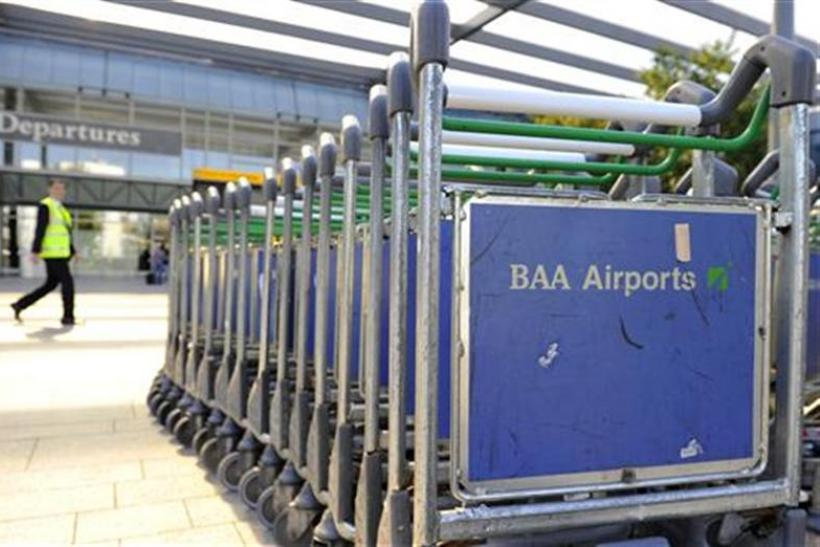 A worker passes luggage trollies at Heathrow Airport in London