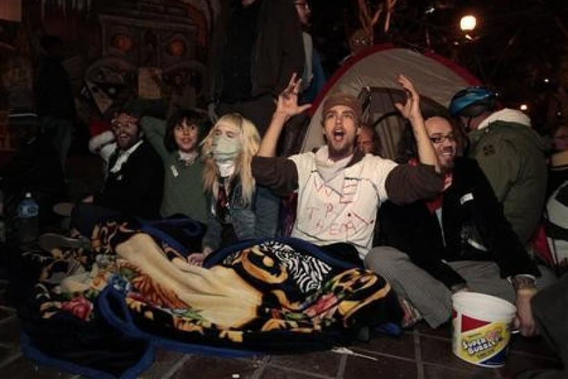 Protesters celebrate after they evaded eviction at the 12.01am deadline outside City Hall at the Occupy LA encampment in Los Angeles
