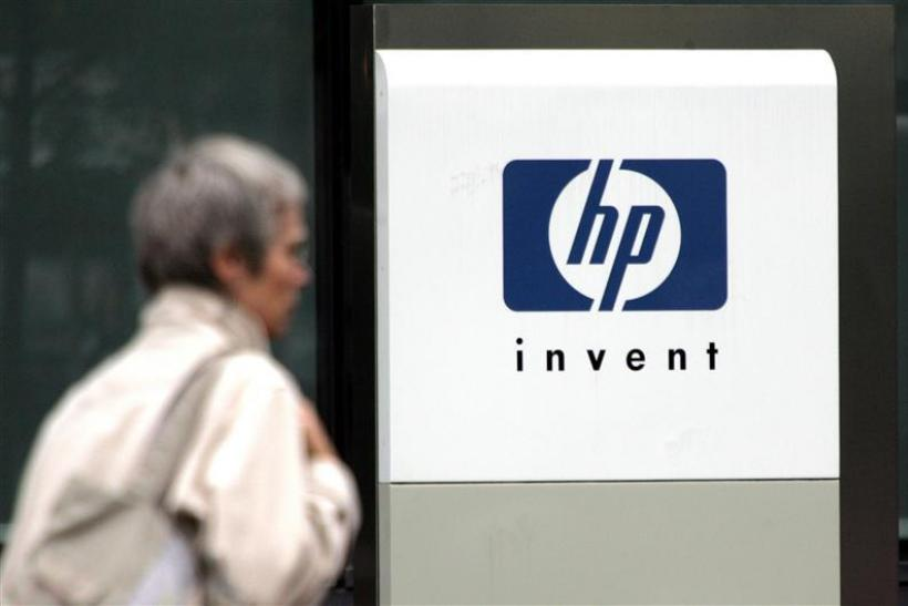 File photograph of a woman walking past the Hewlett Packard logo at its French headquarters in Issy le Moulineaux