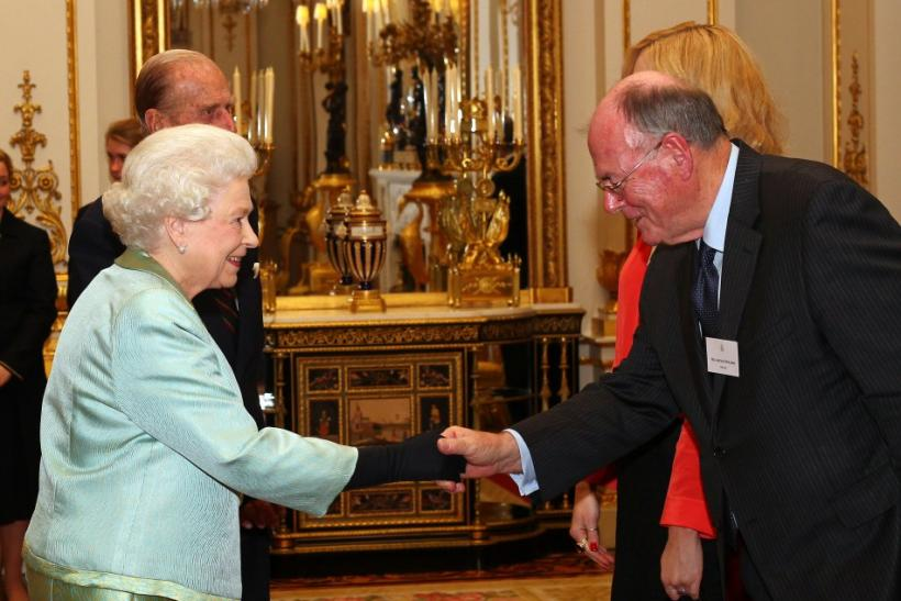 Britain's Queen Elizabeth greets veteran Sun photographer Arthur Edwards (R) during a reception for members of the media at Buckingham Palace in London November 28, 2011.