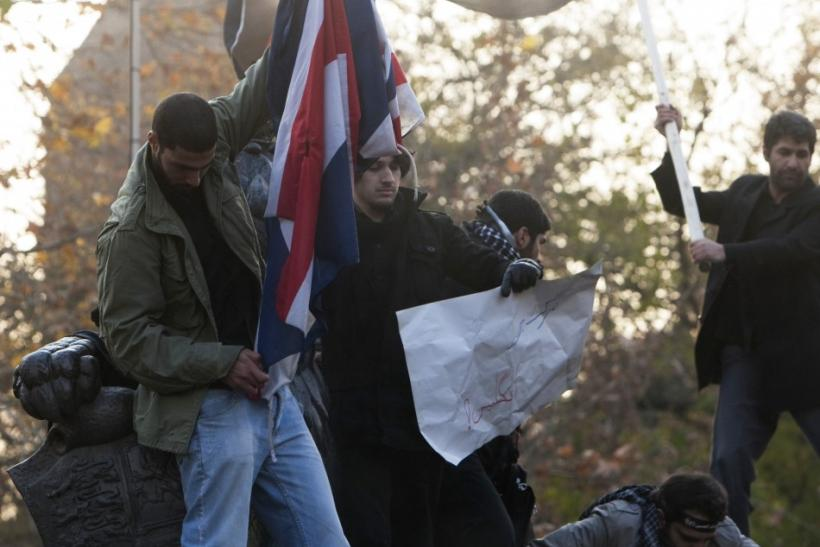 A protester tries to set fire to a British flag on top of a wall at the British embassy in Tehran