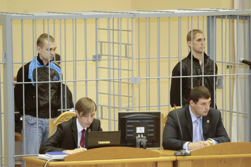 File photo of Konovalov and Kovalyov standing in a guarded cage during a hearing in Minsk