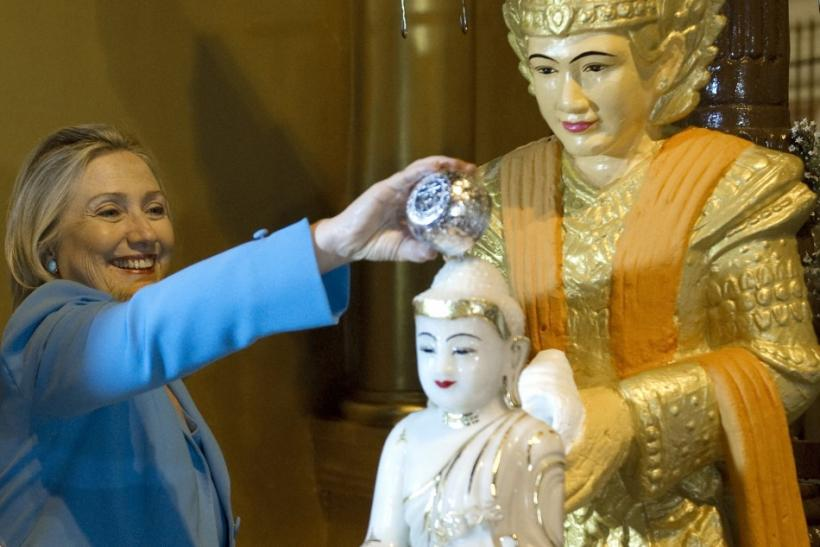 U.S. Secretary of State Clinton pours water over a statue of Buddha at the Shwedegon Pagoda in Yangon