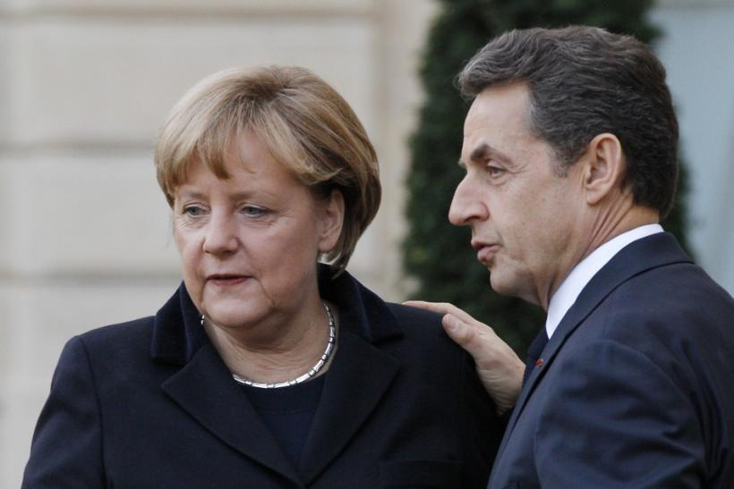 France's President Sarkozy escorts German Chancellor Merkel at the Elysee Palace following a joint news conference in Paris