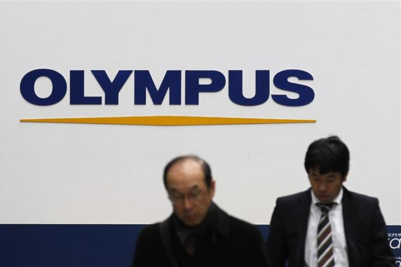 Pedestrains walk past a signboard of Olympus Corp at its showroom in Tokyo