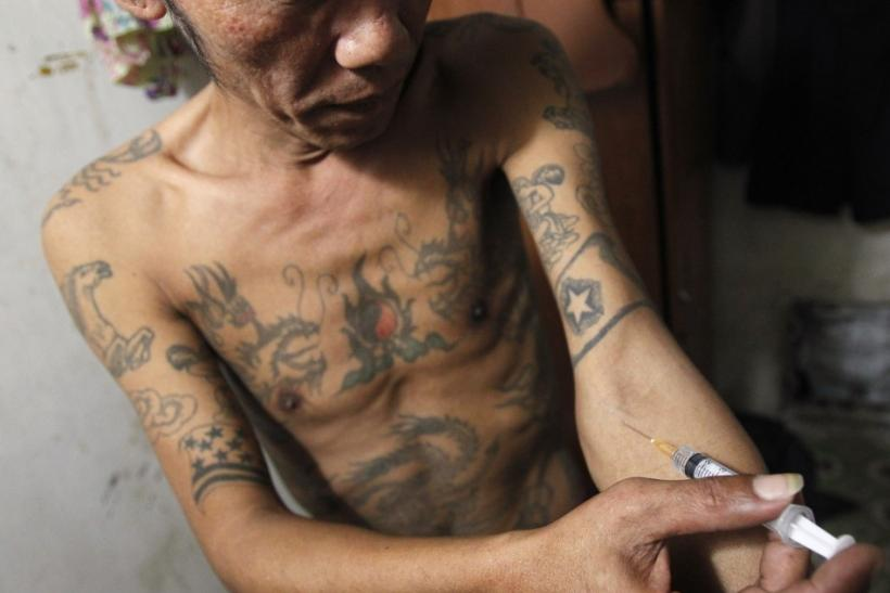 A Man , injects a syringe filled with heroin in his rented room in Hanoi