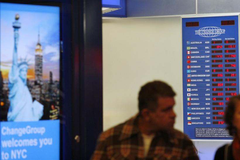 People walk past a board displaying exchange rates in a money exchange house at Times Square in New York