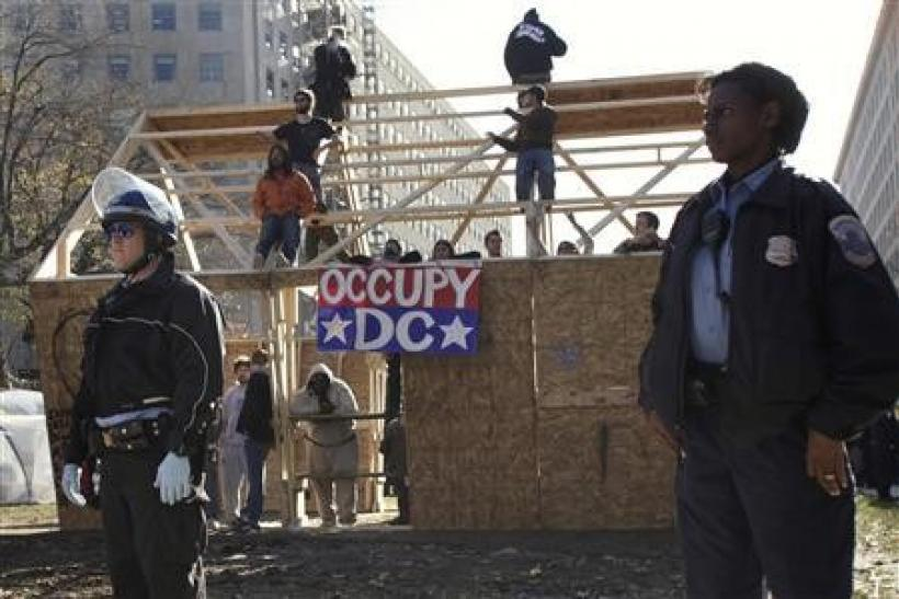 Police officers stand around a structure built the night before by Occupy DC protesters on McPherson Square in Washington