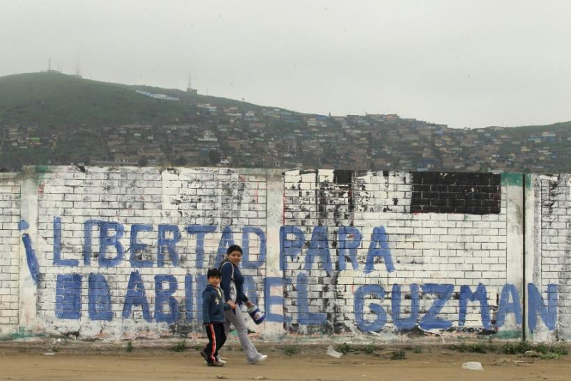 People walk in front of a sign that reads 'Freedom for Abimael Guzman' in a shantytown of Villa El Salvador in Lima