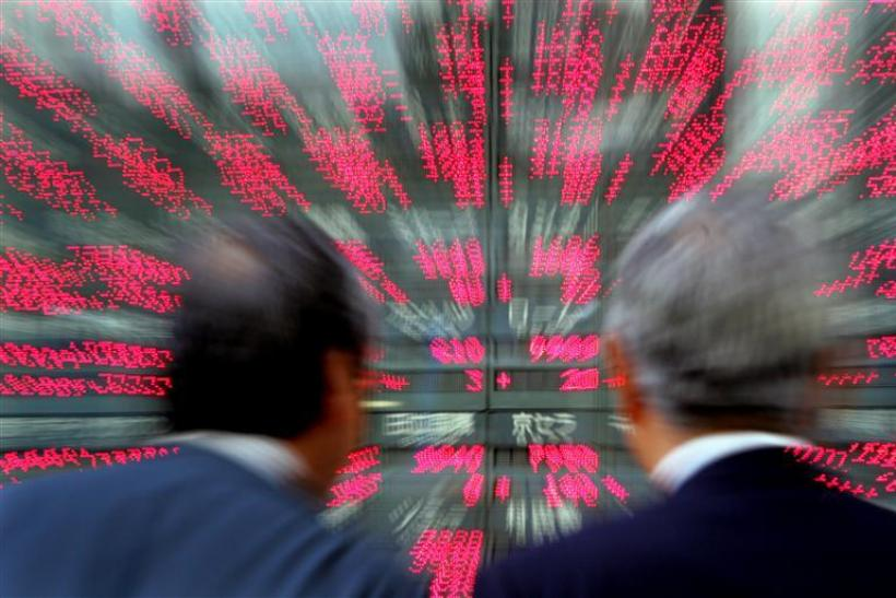 Japanese businessmen look closely at stock prices in Tokyo