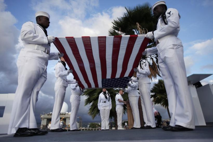 U.S. Navy sailors perform a flag ceremony for Pearl Harbor survivor Lou Soucy, whose remains were being interned on the USS Utah, during a memorial on Ford Island in Honolulu, Hawaii