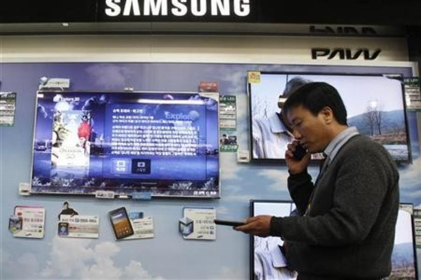 A salesman talks on his mobile phone as he walks past Samsung Electronics' LED television displays at an electronics store in Seoul April 29, 2011.