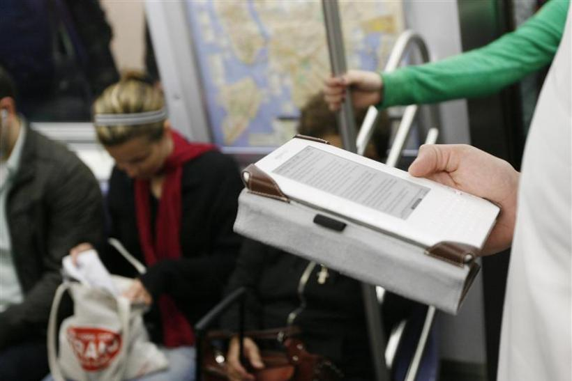 A commuter uses a Blackberry and a Kindle while riding the subway in New York