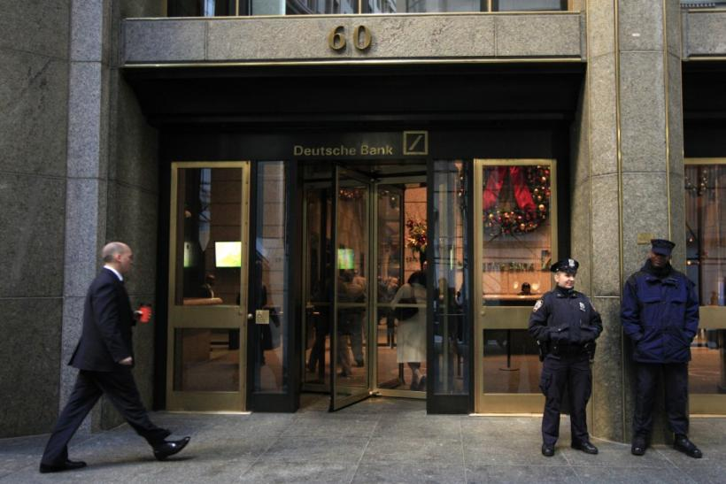 A New York City Police Officer stands beside a security officer at the entrance of a Deutsche Bank office in New York