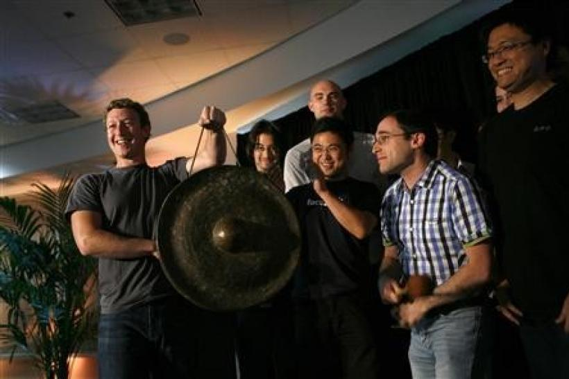 "Facebook CEO Mark Zuckerberg (L) holds a gong while celebrating with members of his staff after unveiling the company's new location services feature called ""Places"" during a news conference at the Facebook headquarters in Palo Alto, Califo"