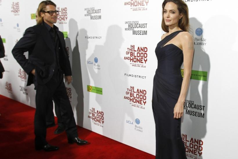 "Director of the movie Angelina Jolie poses, as her partner actor Brad Pitt watches, at the premiere of ""In the Land of Blood and Honey"" at the Arclight theatre in Los Angeles, California"