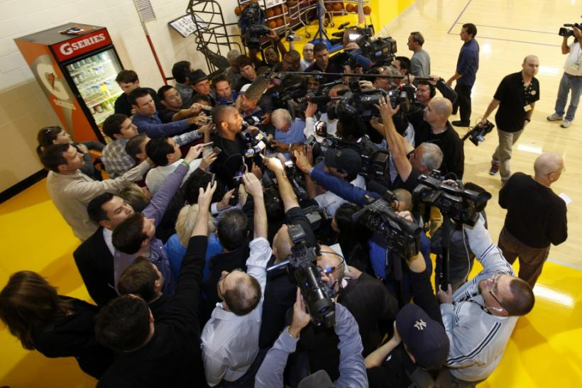 Los Angeles Lakers shooting guard Kobe Bryant (C) is surrounded by members of the media following NBA's opening day of training camp for the Los Angeles Lakers basketball team at their facilities in El Segundo, California