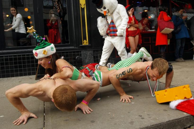 Participants in the annual Santa Speedo Run do push-ups on the sidewalk as someone dressed as a snowman passes by after the run through the streets of the Back Bay neighborhood of Boston, Massachusetts