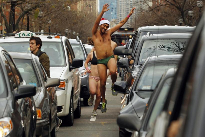 A participant of the annual Santa Speedo Run makes his way between cars stopped on the streets of the Back Bay neighborhood of Boston, Massachusetts