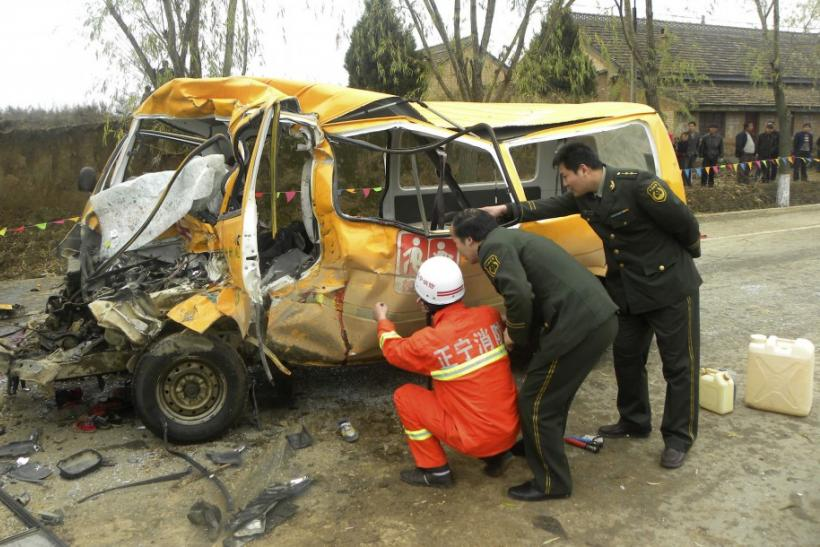 Rescuers inspect a school bus after it collided with a truck at a traffic accident site in Yulinzi township of Zhengning county