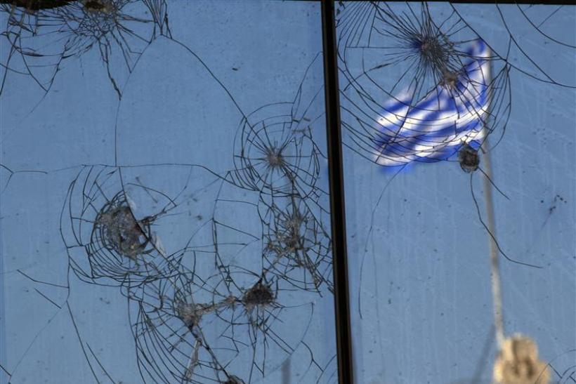 A Greek flag is reflected on a glass building damaged by recent civil unrest in central Athens