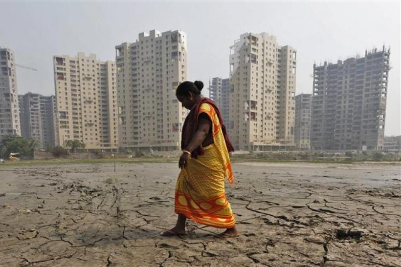 A woman labourer walks past a residential estate under construction in Kolkata