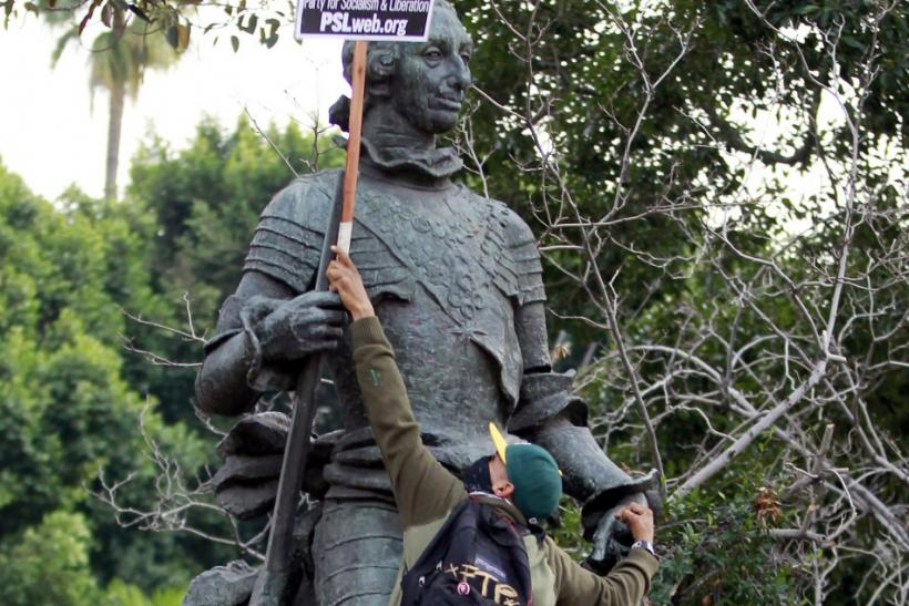Ricky Rios from Pamona, California attempts to place a sign in the arms of a statue of King Carlos III of Spain during an Occupy ICE (Immigration Customs and Enforcement) protest march in Los Angeles