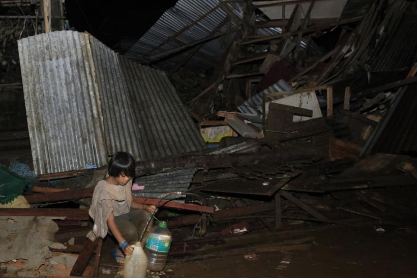 A boy fetches water from a broken pipe among destroyed houses along a road in a village hit by flashfloods caused by typhoon Washi in Cagayan de Oro, southern Philippines, December 17, 2011.
