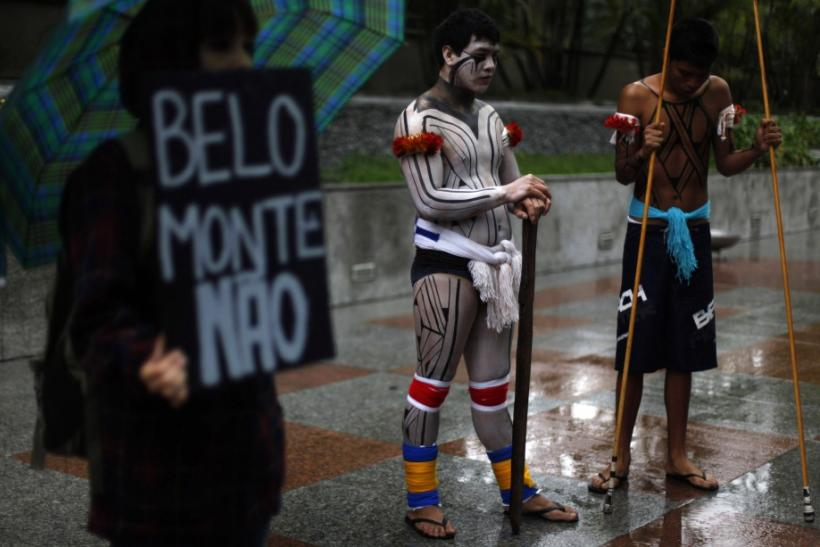 "Brazilian indigenous men stand next to an environmental activist as he holds a banner that reads "" Belo Monte, No"" during a protest in Sao Paulo"