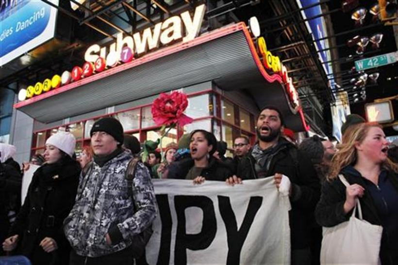 Protesters affiliated with the Occupy Wall Street movement hold a banner as they walk on the street during a protest in New York