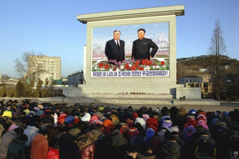 North Koreans bow in front of portraits of North Korea's founder Kim Il-sung (L) and his son and leader Kim Jong-il in Pyongyang