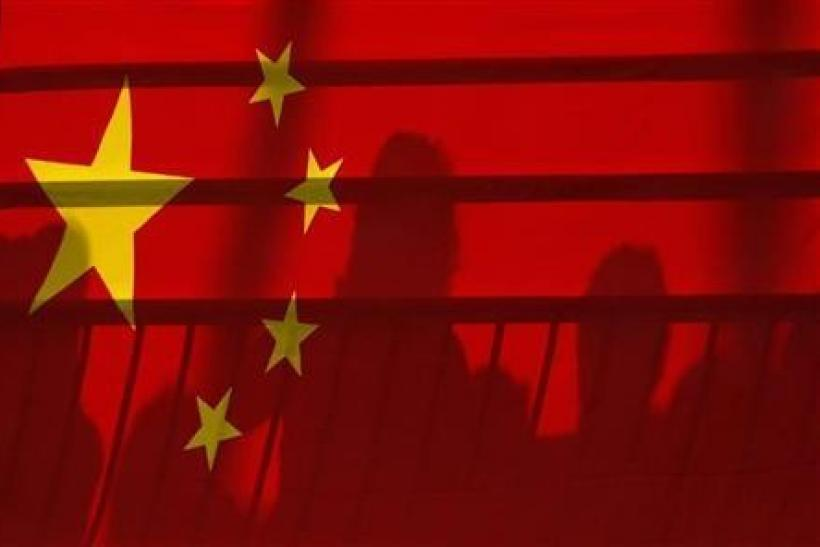 The shadows of spectators are seen through a Chinese national flag at the Beijing 2008 Olympic Games, August 12, 2008.