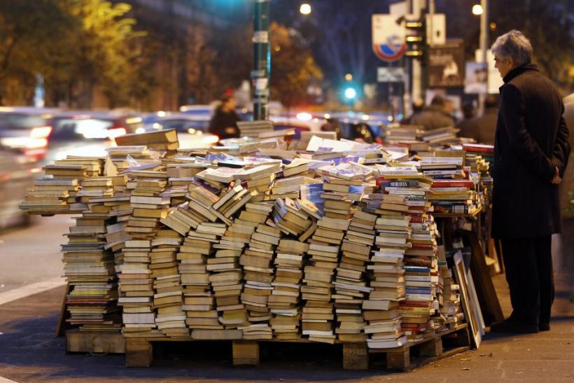 A man looks at books on display at a stall in downtown Rome